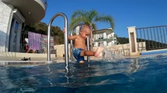 Stock Video Footage of Toddler stands on the ladder to swimming pool 2