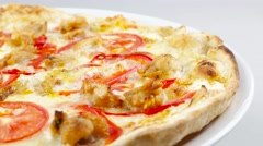 Edge of pizza with chicken and tomatoes rotates on the white plate Stock Footage