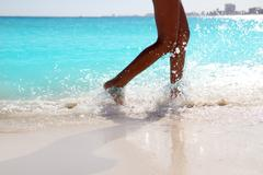 Woman legs walking splashing beach aqua water Stock Photos