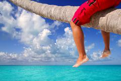 Caribbean inclined palm tree beach tourist legs - stock photo