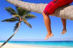 Caribbean inclined palm tree beach tourist legs Stock Photos