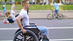 7 in 1 video Invalid man sit and ride in wheel chair in crowd stream at sidewalk Stock Footage