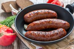 Grilled sausages in frying pan and a ripe tomato. Stock Photos