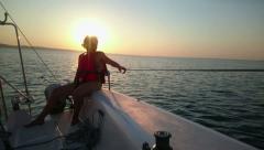 Two women sailing yacht, enjoying sea voyage, beautiful sunset, active rest Stock Footage