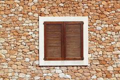 brown wooden window in masonry wall - stock photo
