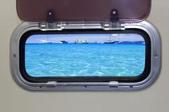 Boat porthole turquoise tropical blue ocean sea - stock photo