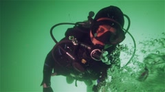 Bubbles in slow motion rise to diver in green water Stock Footage