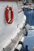 White boat side with fender and round lifesaver Stock Photos