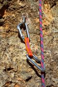 climbing shackles and rope on a rock wal - stock photo