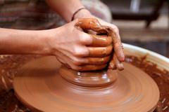 Clay potter hands closeup working on wheel handcrafts Stock Photos