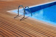 blue swimming pool with teak wood flooring - stock photo