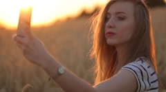 Gorgeous blonde is smilling and making selfie with her smartphone in the rye fie - stock footage