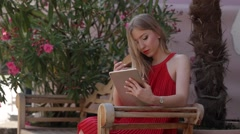 Beautiful blonde is sitting outside and checking something in her tablet Stock Footage