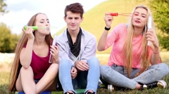 Stock Video Footage of Friends having fun and blowing soap bubbles in park