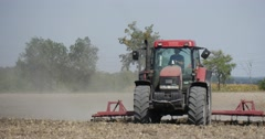 Tractor is Plowing The Soil With Plow Flying Dust Field Trees on a Horizon Stock Footage