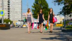 Three friends, young girls on street of big city with shopping bags, defocused. Stock Footage