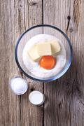 Bowl of flour, egg yolk and butter - stock photo
