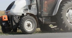 Man in Workwear is Driving the Tractor With Green Trailer And Plow is Driven by Stock Footage