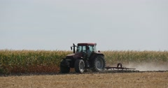 Man is Driving the Tractor With Plow is Plowing The Soil Plants are Growing on Stock Footage