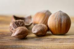 hazelnut and nutshell on wood - stock photo