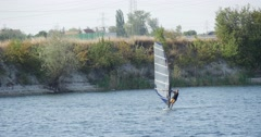 Man on The Windsurf Board With Sail is Floating Fast by Watery Surface along - stock footage