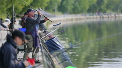 A lot of fishermen on the river bank in the city park. Stock Footage