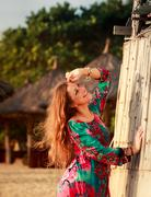 Stock Photo of slim girl in colorful by reed wall against defocused background