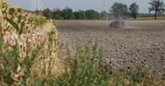 Tractor Distantly is Plowing The Field Black Soil Flying Dust Behind the Stock Footage