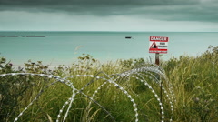 Memorial beach and barbed wire at Arromanches, France Stock Footage