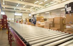 Package conveyor belt for distributing packages in DHL storehouse - stock photo