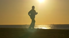 Person jogging exercising in park with sun behind slowmo Stock Footage