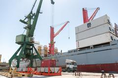 Port crane lifting container and loading ship with cargo Kuvituskuvat
