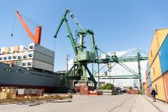 Port crane loading container ship with cargo Kuvituskuvat