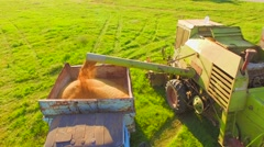 AERIAL VIEW. Combine Harvester Unloads Wheat Grain Into the Truck Stock Footage