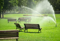 Pouring water in the park against heatwave and high temperature Stock Photos