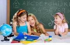Happy laughing kids student girls at school classroom Kuvituskuvat