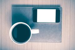 smart phone and coffee cup on book vintage style - stock photo