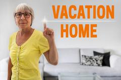 Vacation home touchscreen is shown by senior Stock Photos