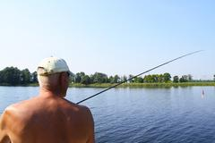 Fisherman with Spinning Catching a Big Fish - stock photo