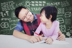 Male teacher teach little girl in class - stock photo