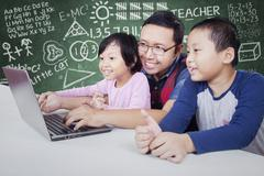 Male teacher teach two students with laptop - stock photo