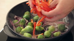 Chef is Salting Red Paprika, Brussel Sprouts and Onions Frying on a Pan Stock Footage