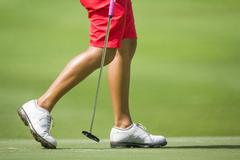 Female golfers walking on green with putter. Stock Photos