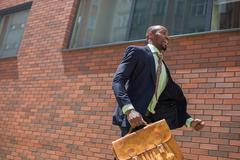 african black young businessman running in a city street - stock photo