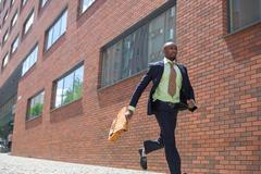 African black young businessman running in a city street Stock Photos