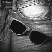 sunglasses on jean pants black and white tone color style - stock photo