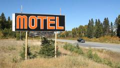 Old orange Motel sign by side of road. Traffic passes. Stock Footage