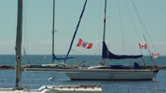 Boat docked at the marina by the lake. Canadian flag is seen waving . 4K UHD. Stock Footage
