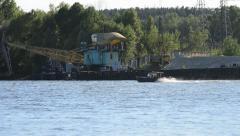 Crane unloads sand and motorboat navigates Stock Footage
