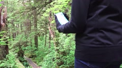 Alaskan Rain Forest, woman using GPS on smart phone Stock Footage